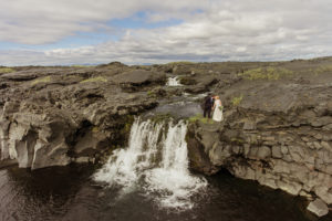 Rachel and John standing on top of a lava rock waterfall kissing in Iceland