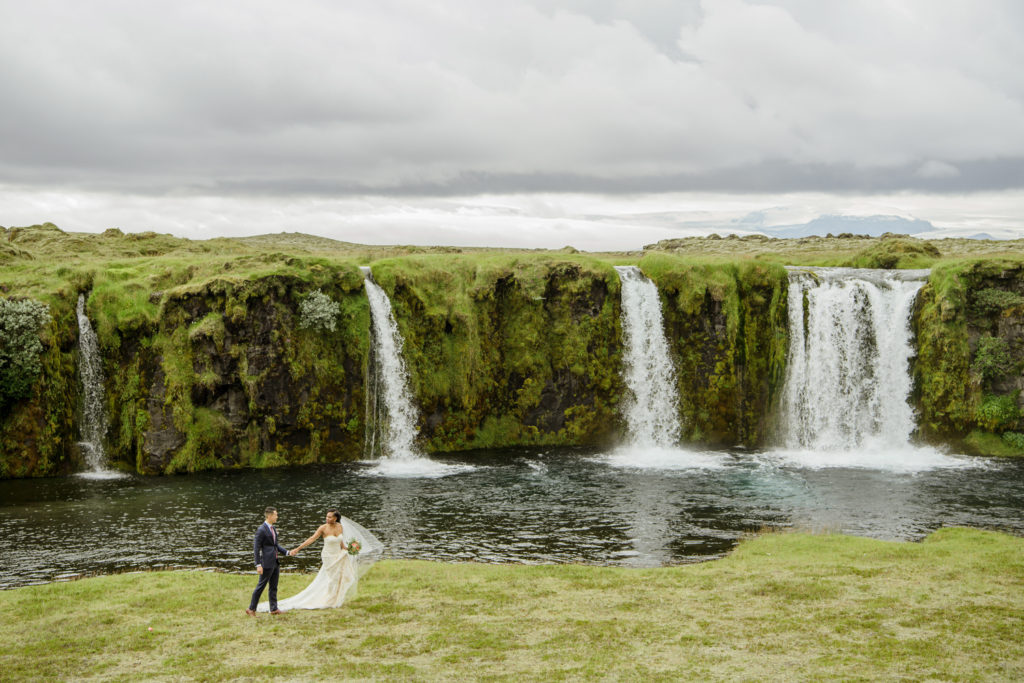 Couple walking in front of a private waterfall in Iceland