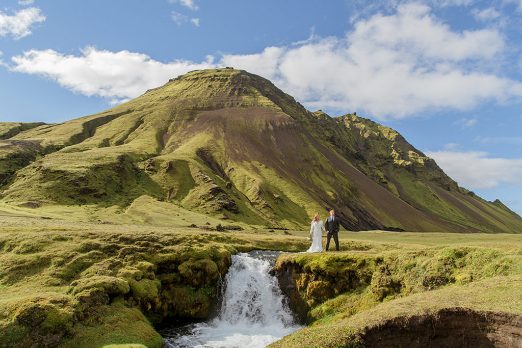 Couple standing on top of a waterfall during their elopement in Iceland