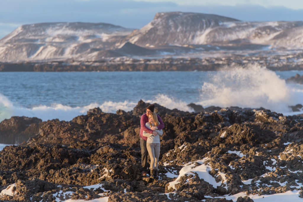 Couple standing on lava rocks with the ocean behind them in Iceland for their engagement session