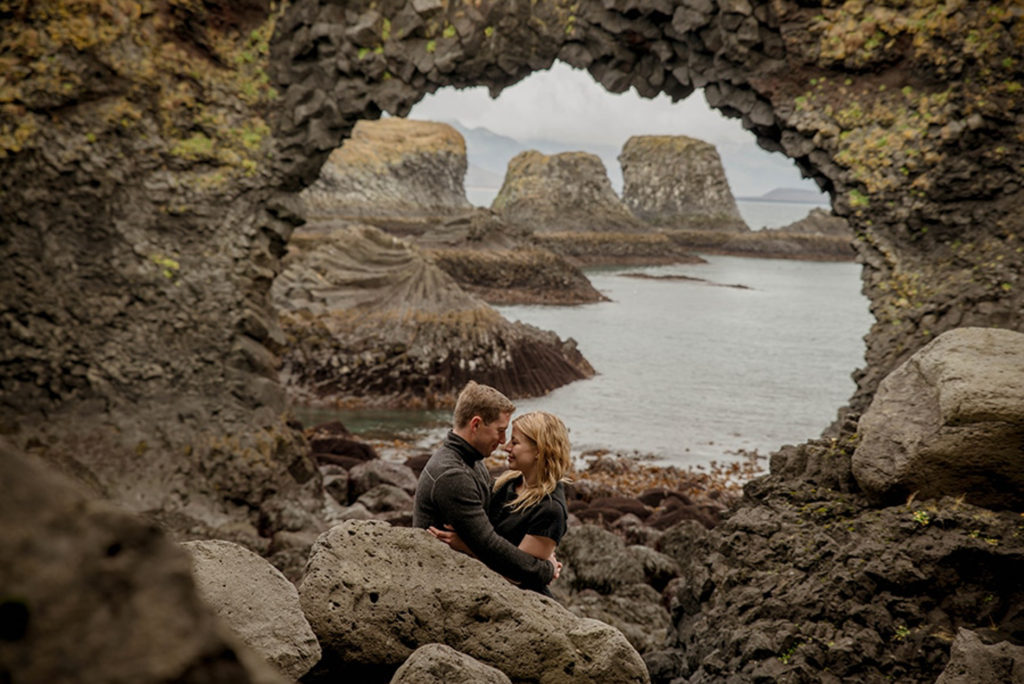 Couple looking at each other at Arnarstapi during their Engagement Session in Iceland