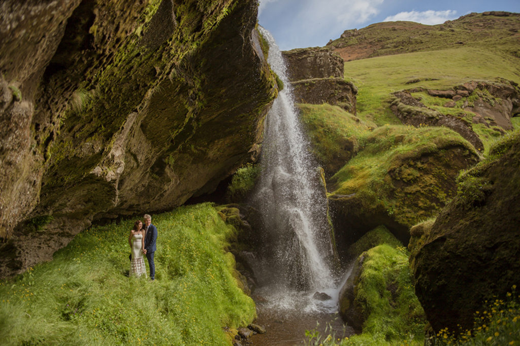 Couple standing behind a super green private waterfall in Iceland