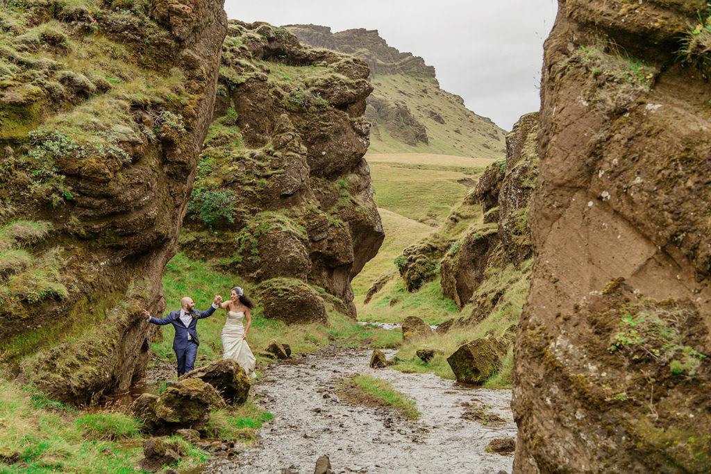 Couple adventuring on their wedding day through a canyon