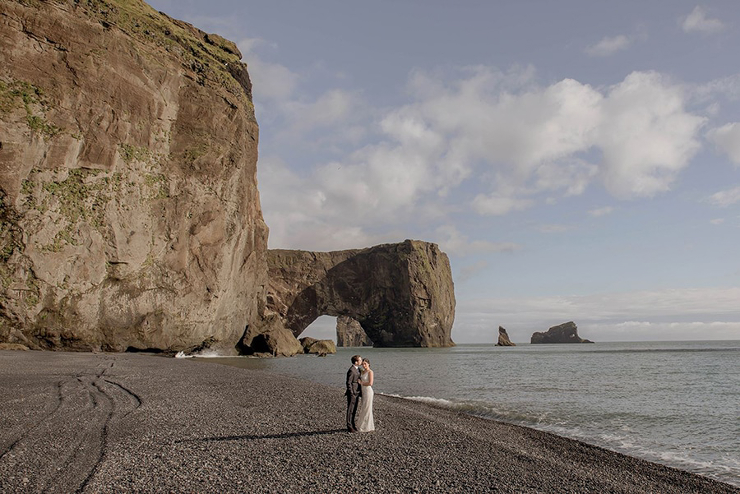 Wedding couple standing in front of the Dyrholaey Sea Arch on the black sand beach