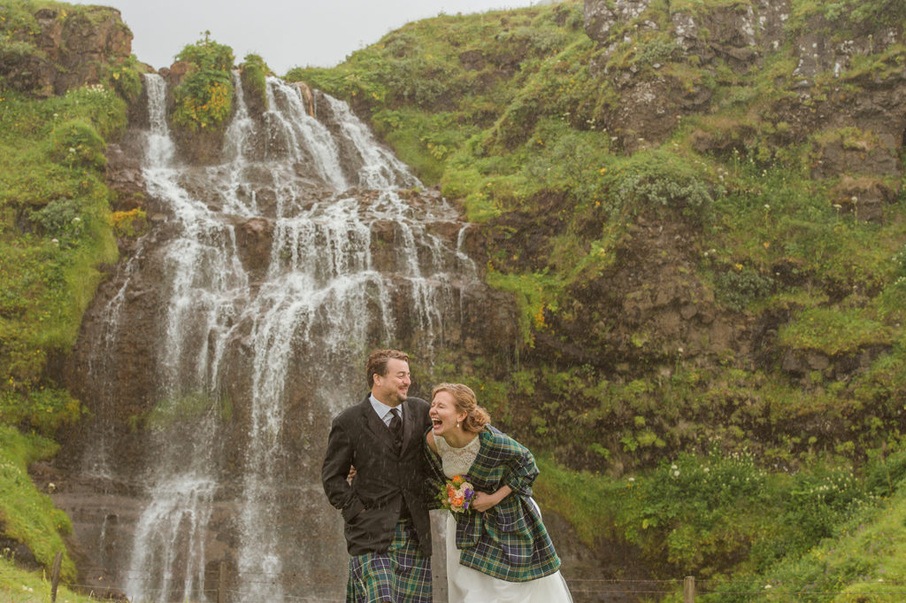 Couple laughing in front of a waterfall while it's raining on their Wedding day in Iceland