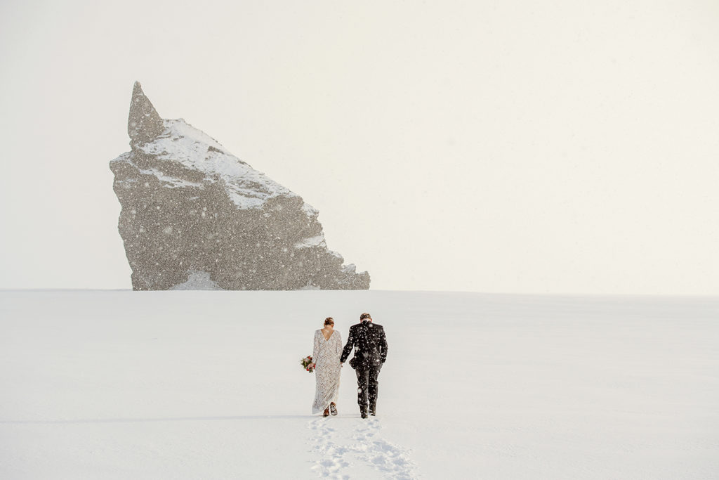 Couple walking through a blizzard during their February Elopement in Iceland