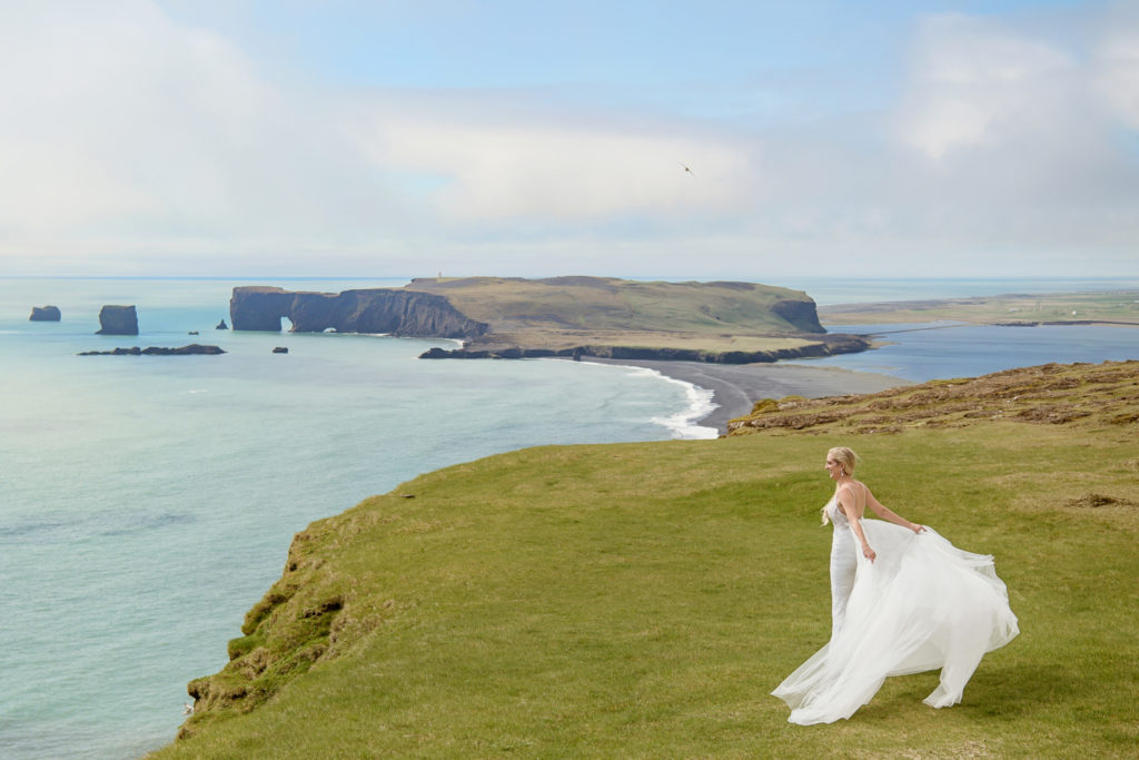 Bride on top of Reynisfjall Mountain overlooking Dyrholaey in the background