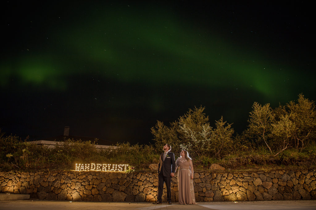 Couple standing under the Northern Lights with a Wanderlust Marquee Sign