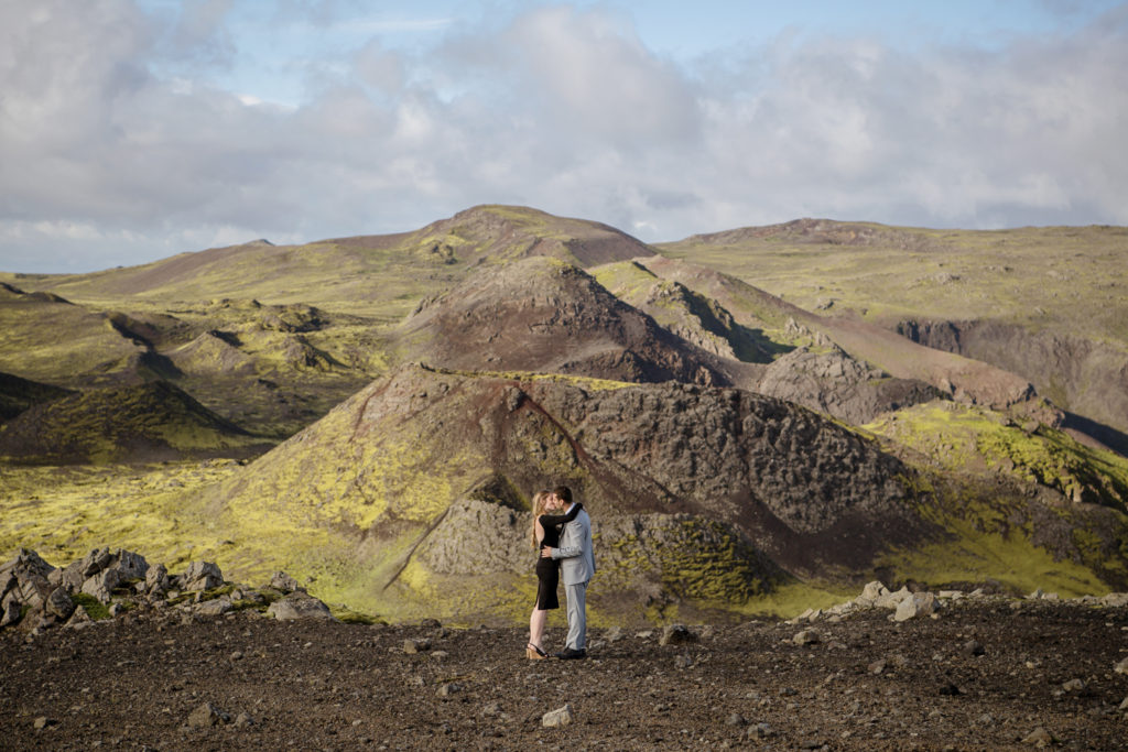 Couple on top of a mountain kissing after a helicopter proposal