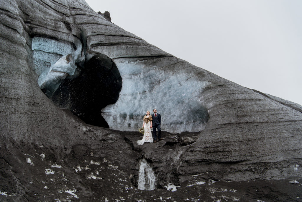 Couple standing in front of an ice cave on their wedding day in Iceland