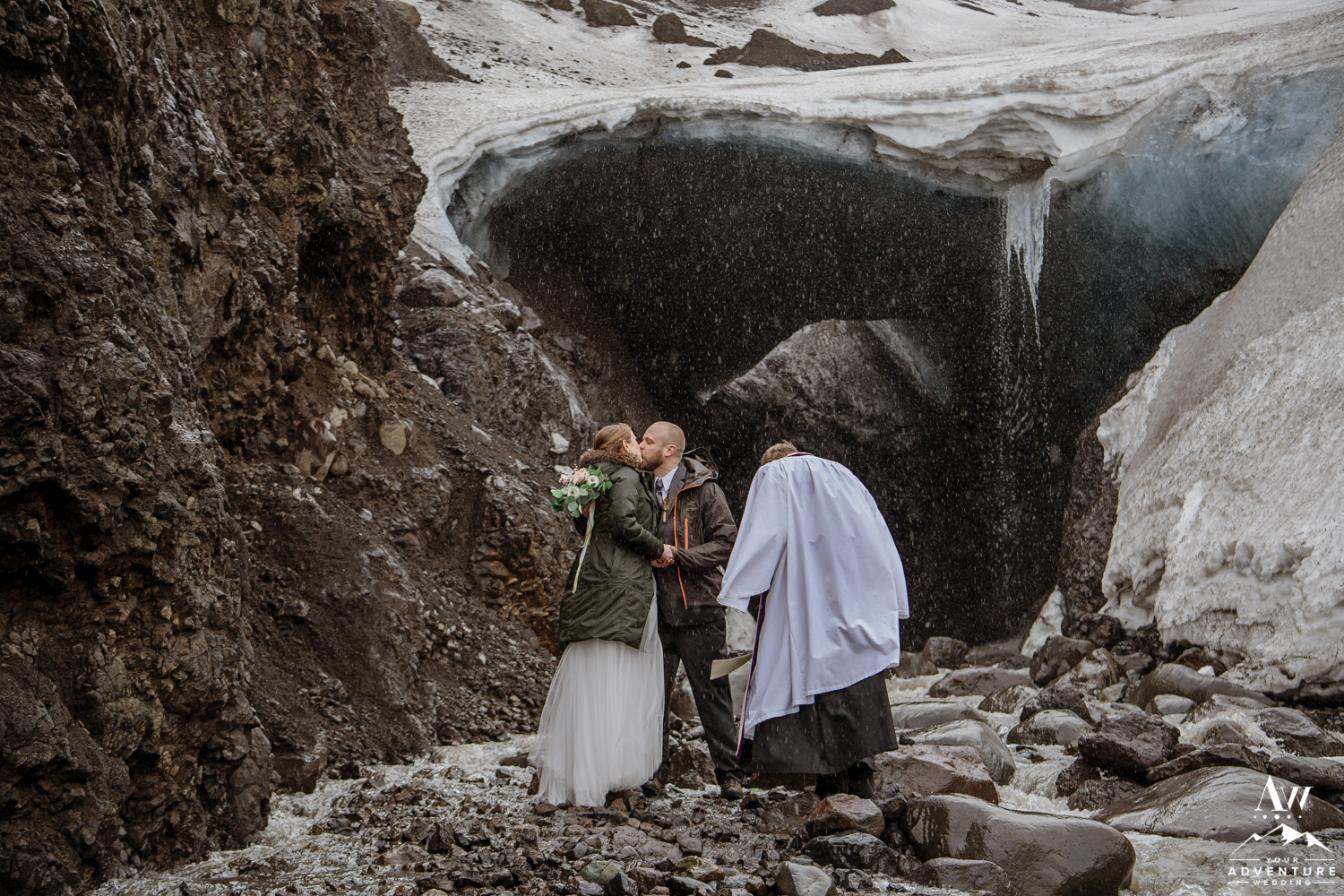 Couple kisses in front of an ice cave during wedding