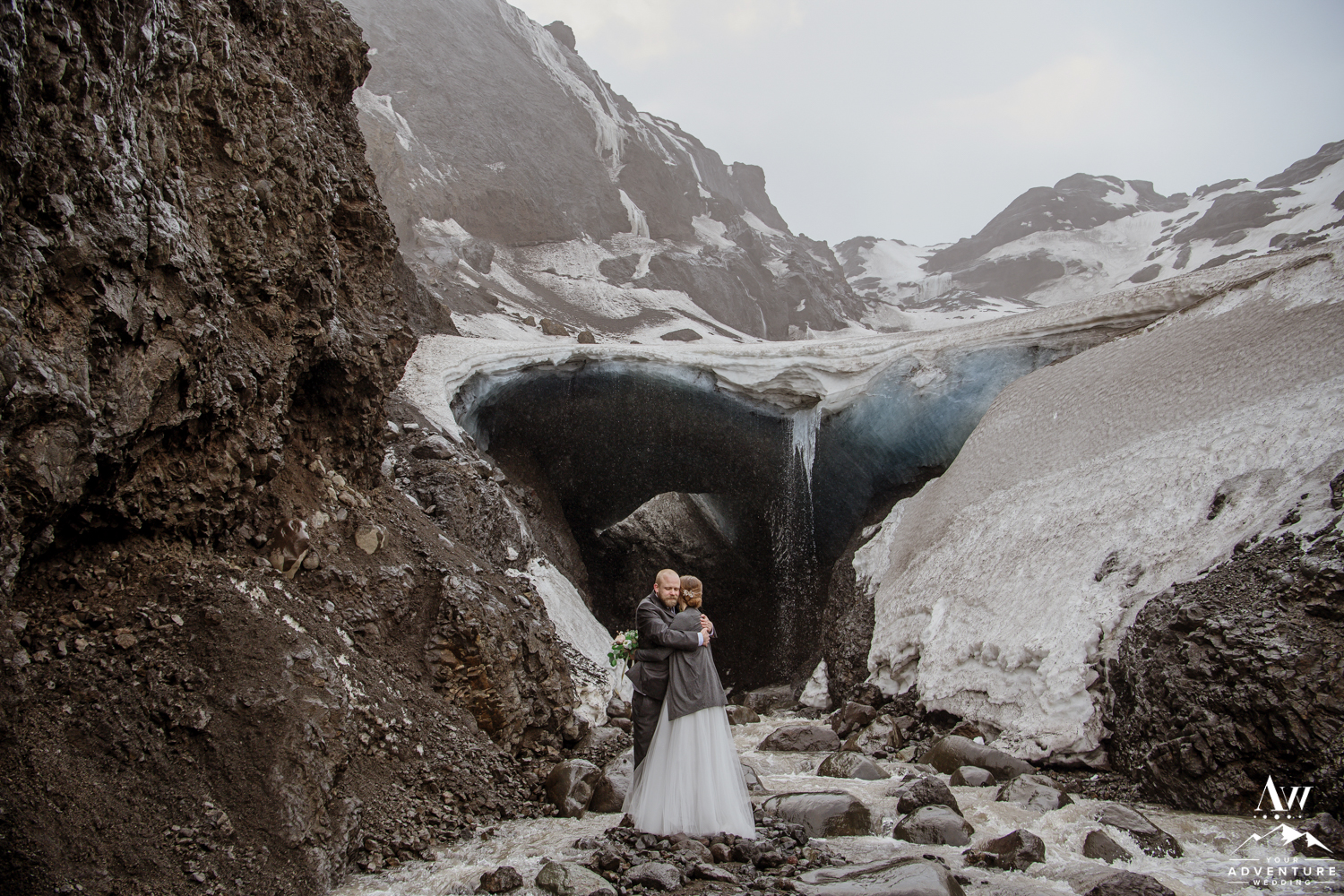 Couple hugging in front of an ice cave in Iceland