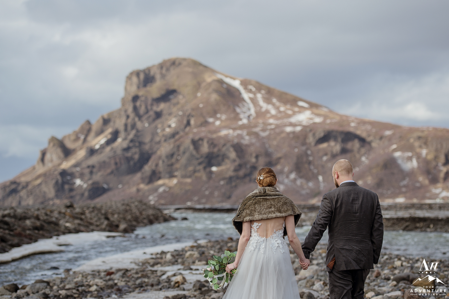 Adventurous Couple hiking by a river on wedding day
