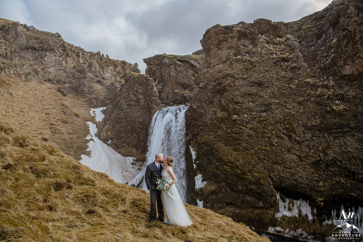 Iceland Elopement Couple kissing in front of a secret waterfall