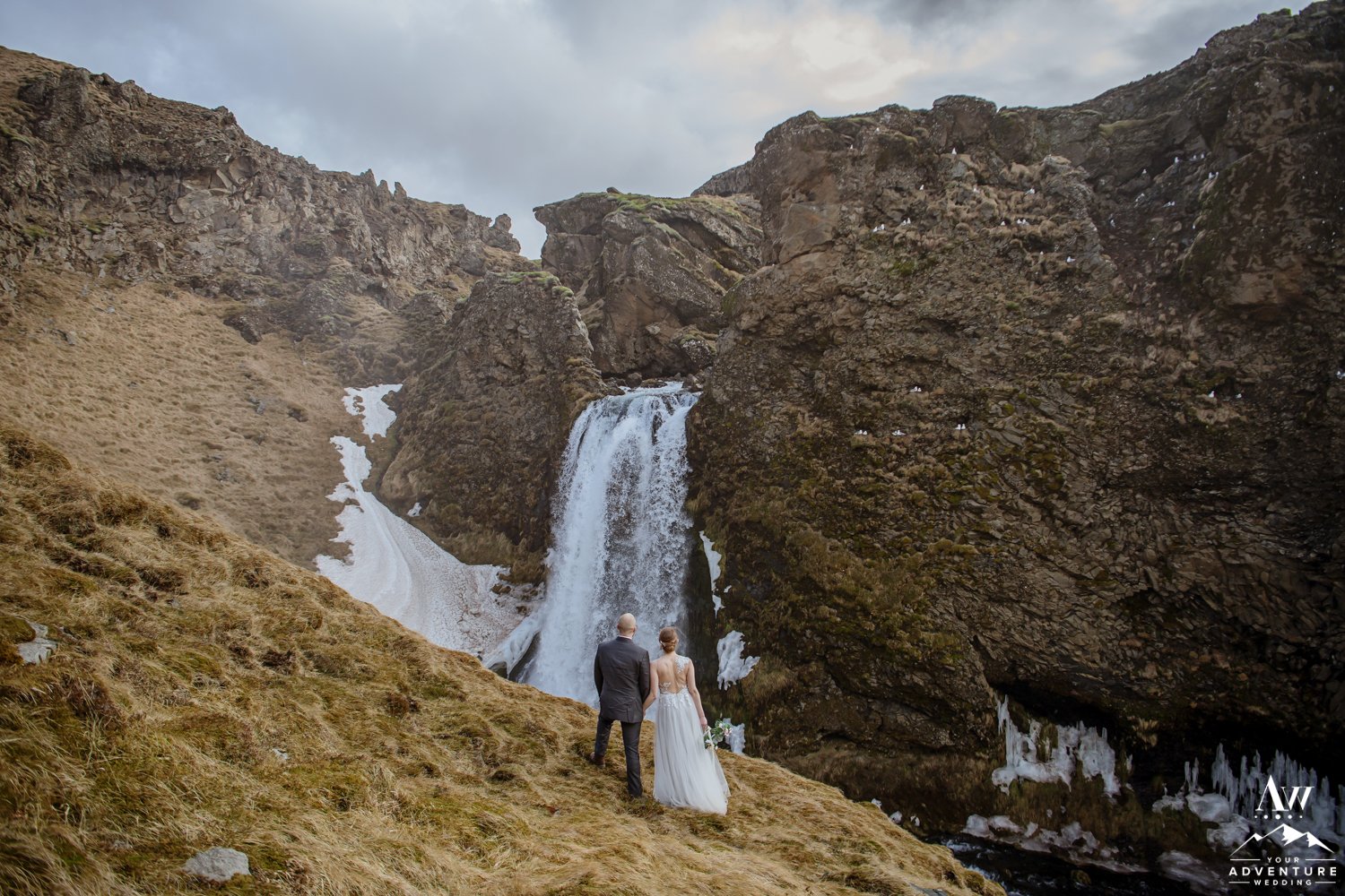 Couple standing in front of a hidden waterfall during Iceland Wedding