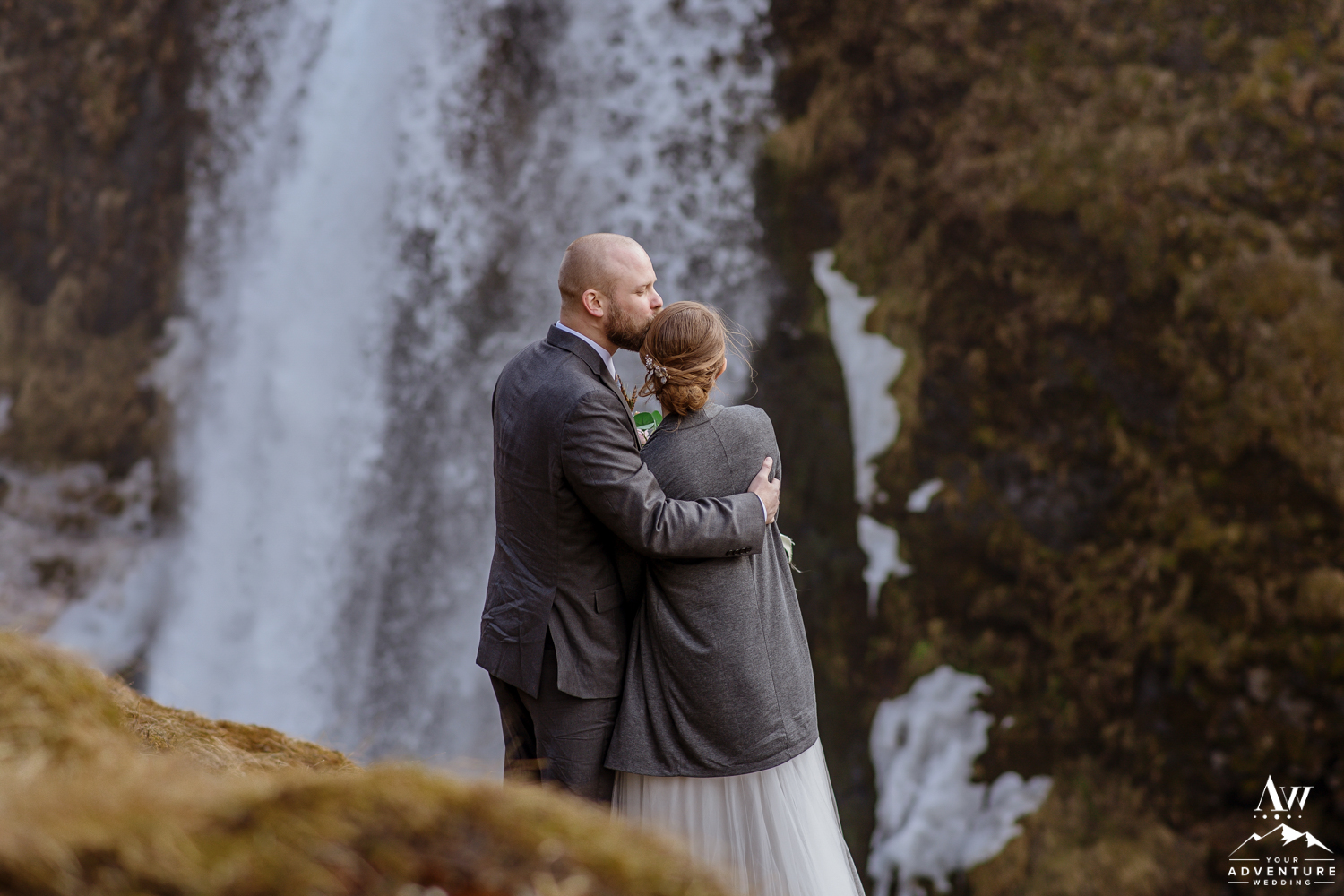 Groom kisses bride in front of hidden waterfall in Iceland