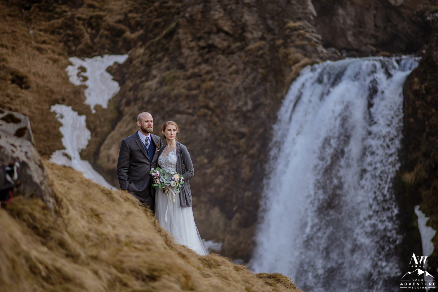 Adventurous Hiking Elopement Couple in front of a waterfall in Iceland