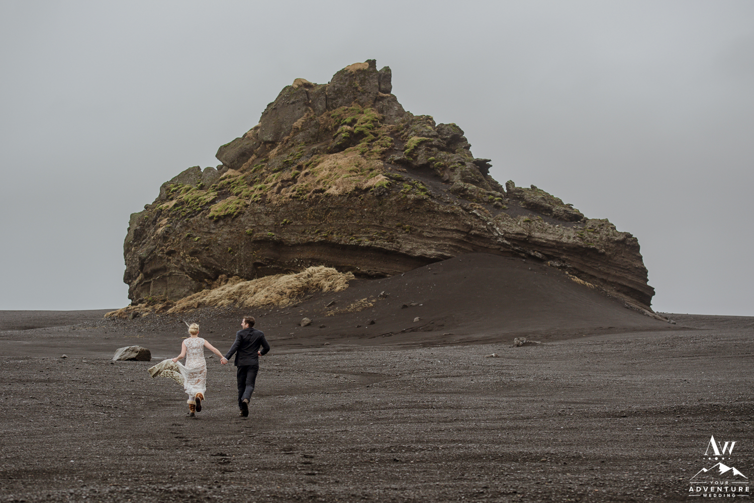 Couple running on black sand beach