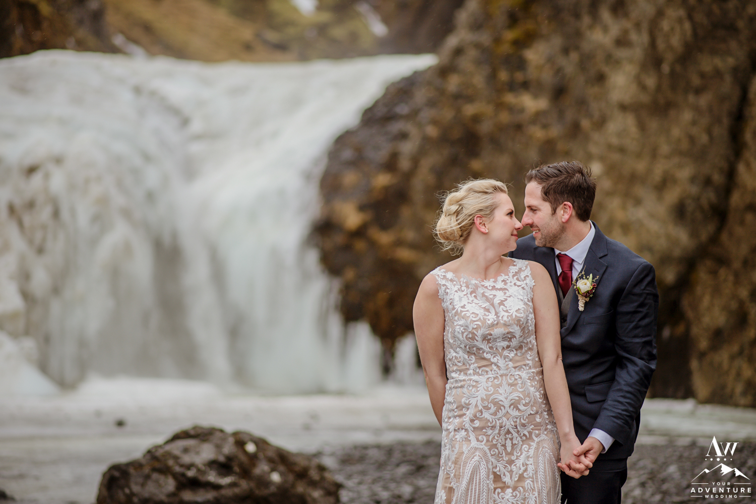 Couple looking at each other on Iceland Elopement Waterfall