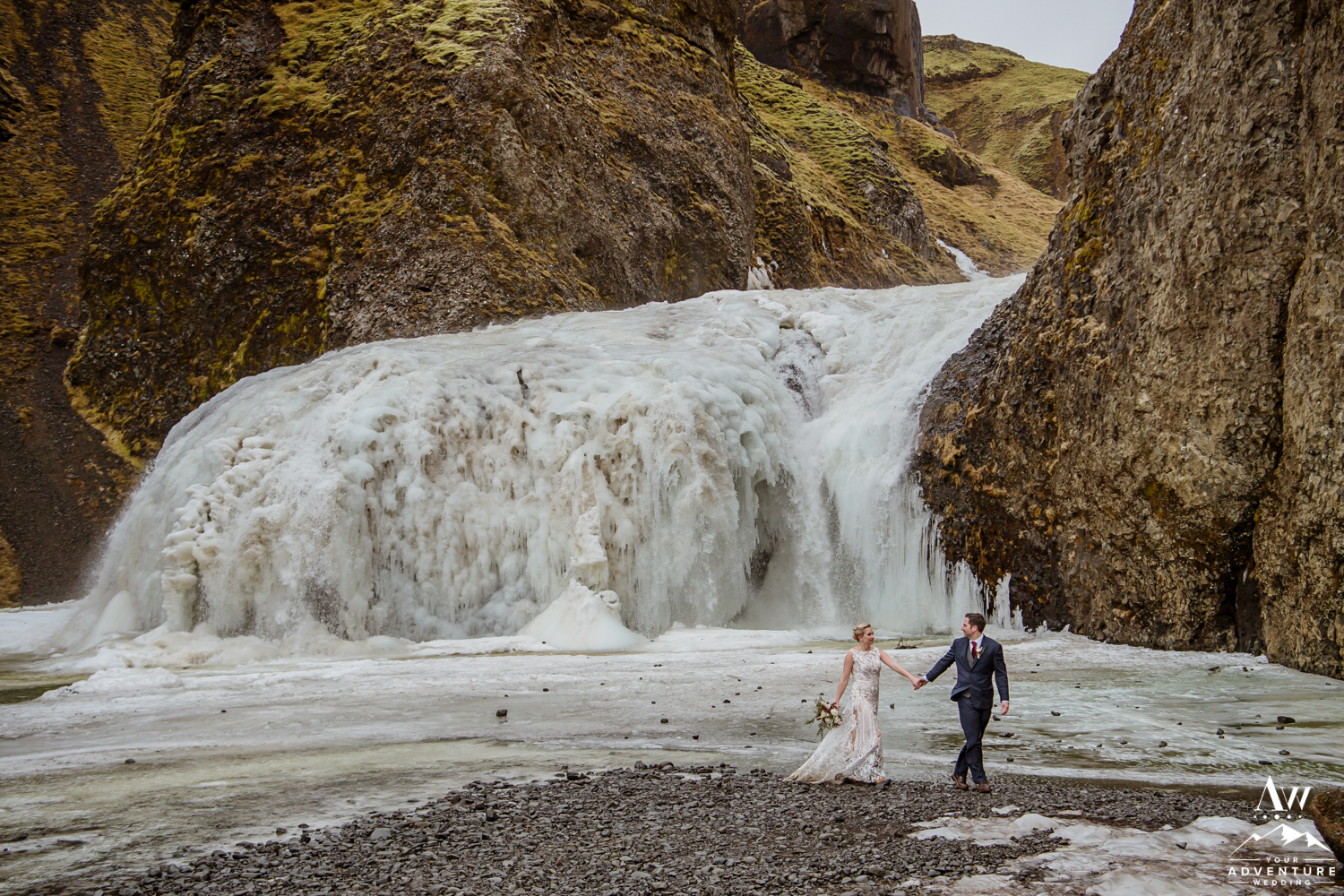 Couple Walking in front of a frozen waterfall in Iceland