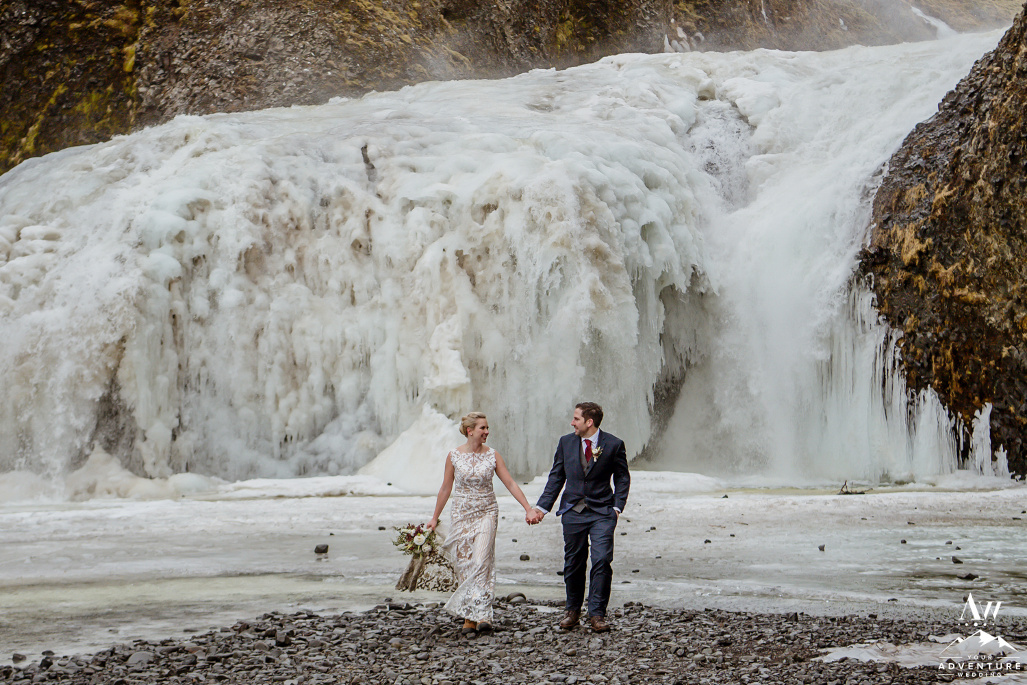 Couple walking in front of a waterfall during their Iceland Elopement