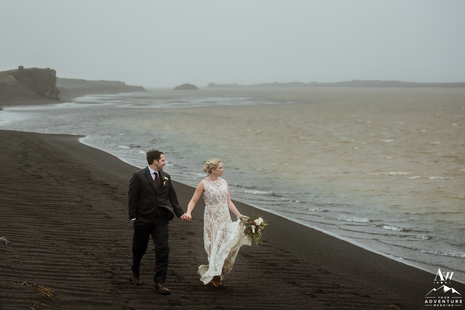Couple walking on black sand beach