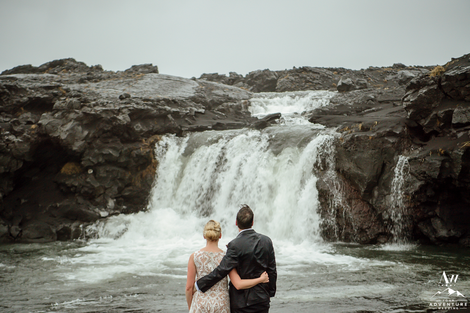 Iceland Elopement Couple looking at a waterfall