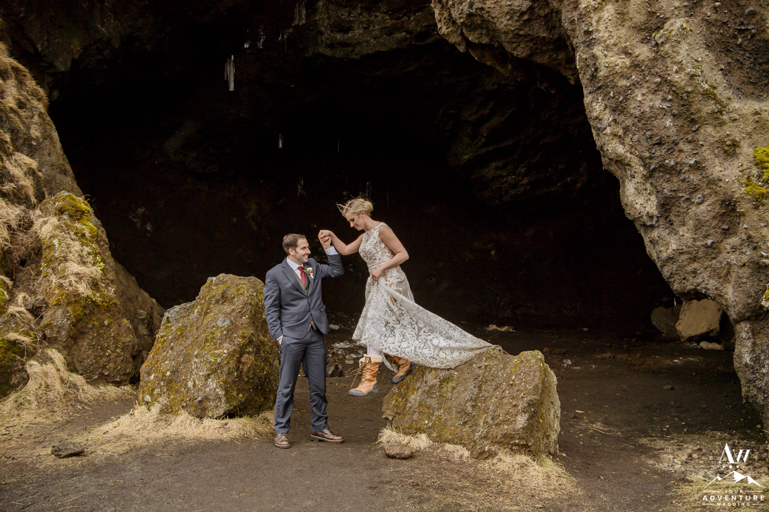 Groom helping his bride down on Iceland Elopement