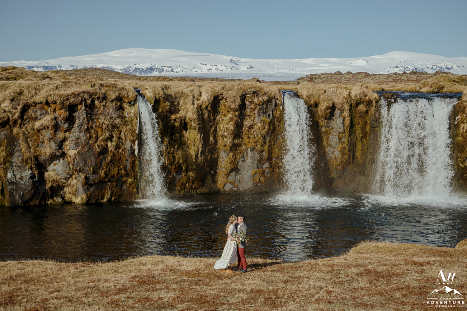 Couple kissing in front of a private waterfall in Iceland