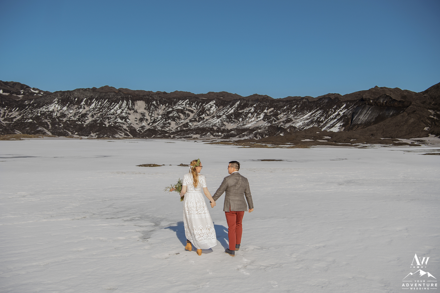 Couple walking to a black glacier in Iceland