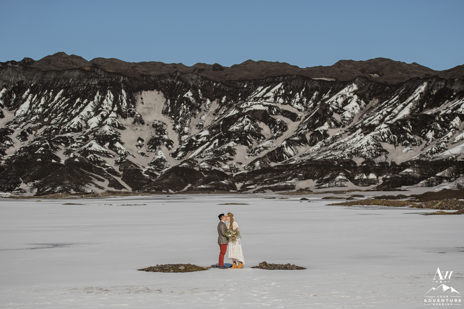 Couple kissing in front of a black glacier in Iceland