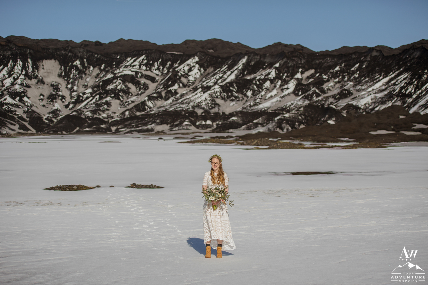 Bride holding her bouquet in front of a black glacier
