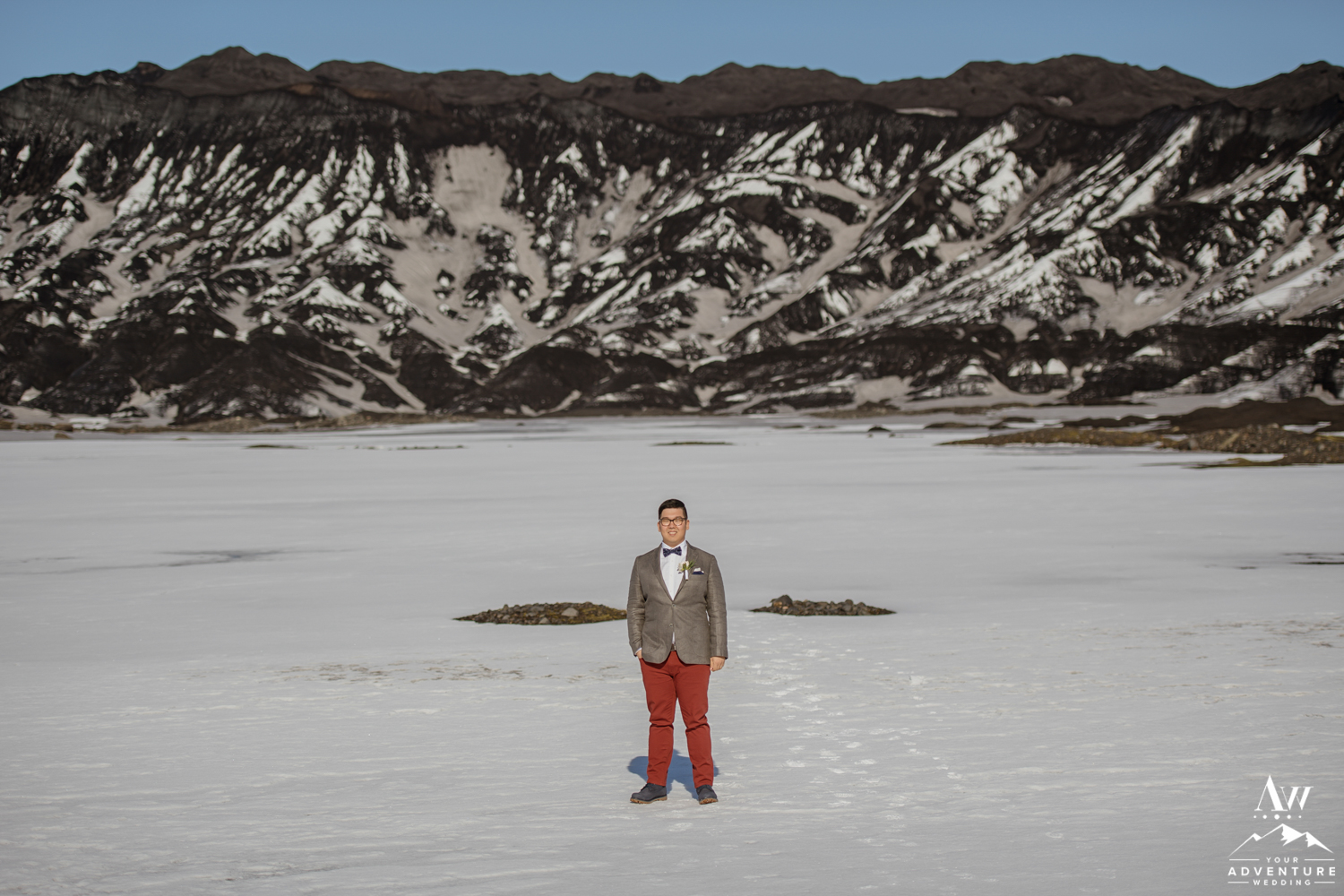 Groom Standing in front of a black glacier in Iceland