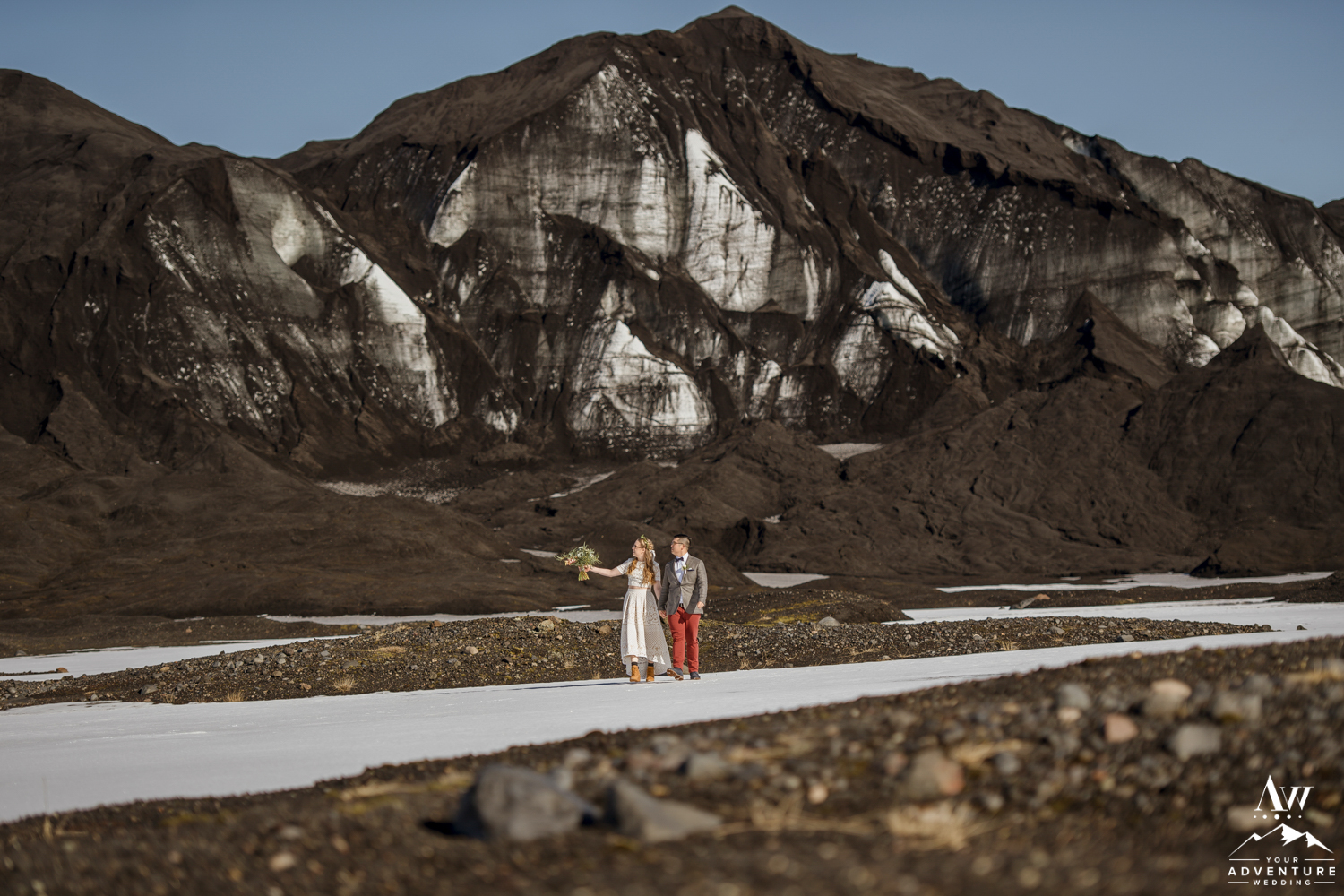 Couple adventuring on their wedding day at a glacier