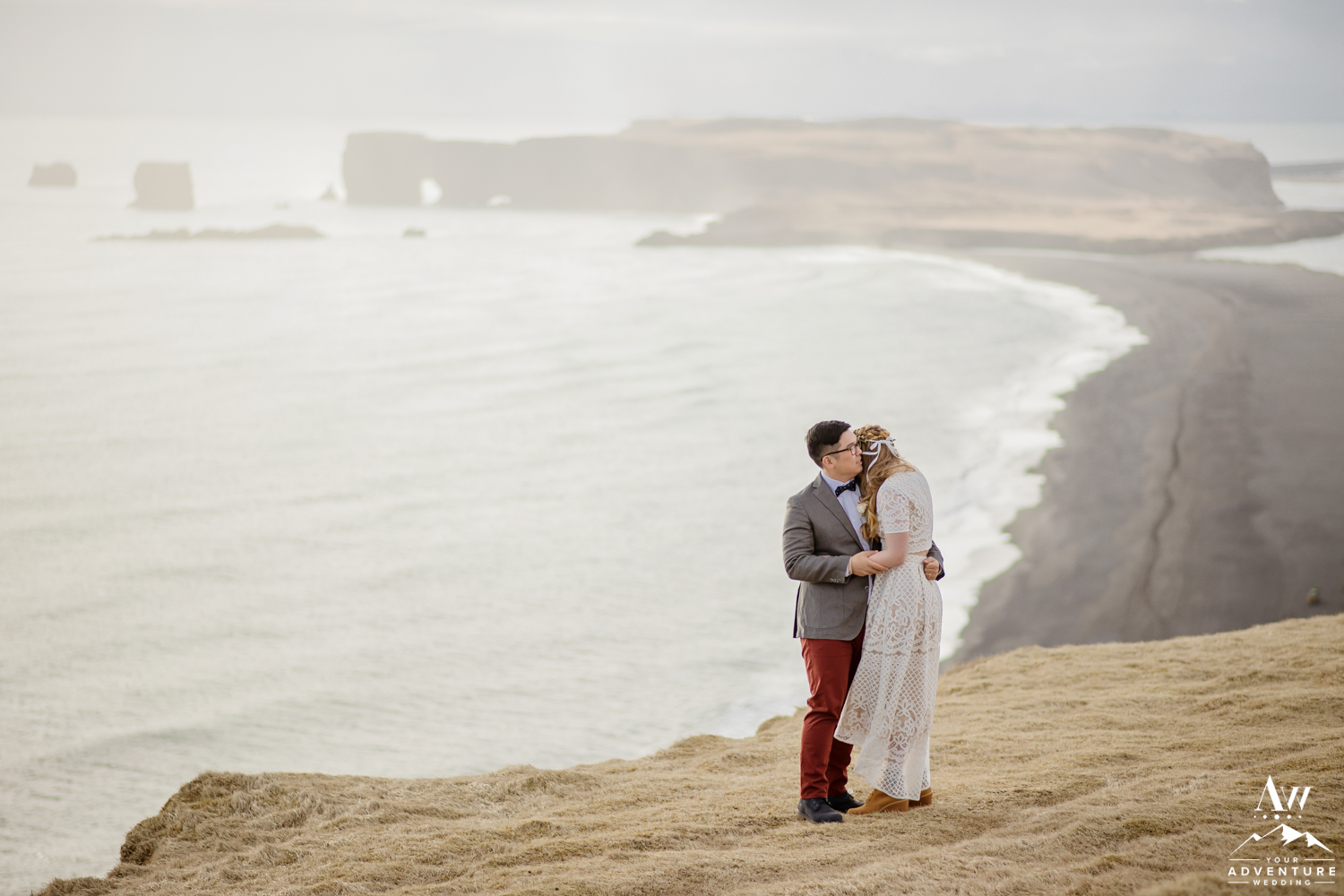 Iceland wedding couple hugging with Dyrholaey in the background