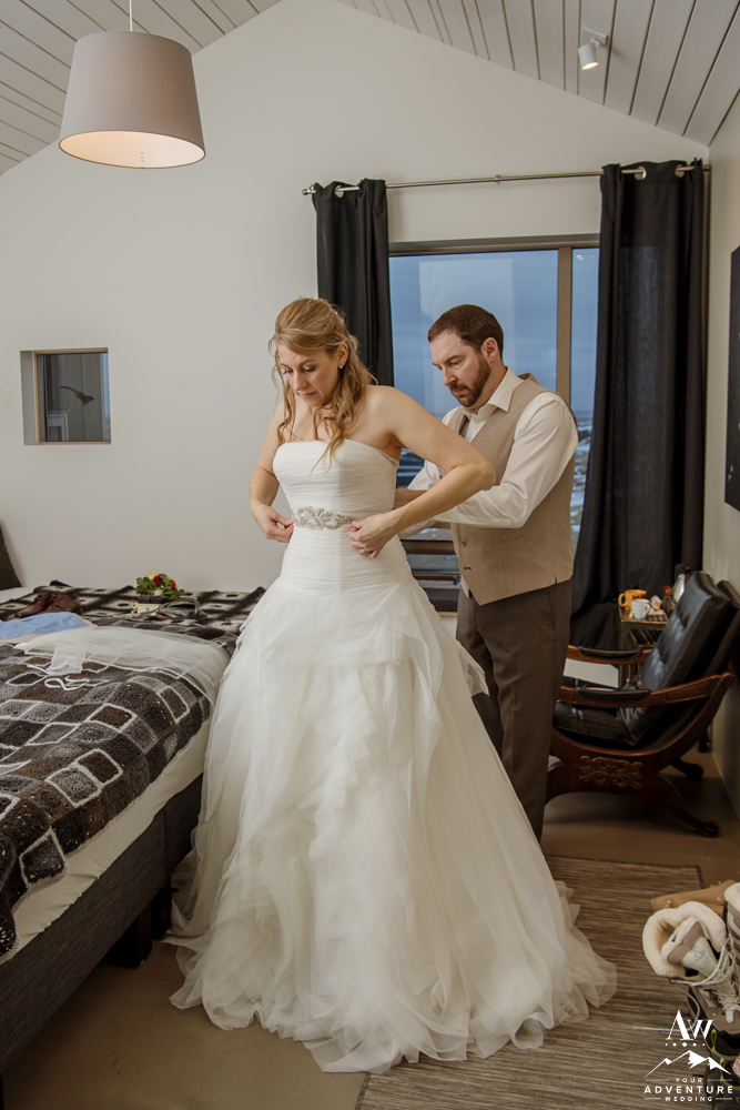 Groom helping his bride get ready for Iceland Elopement