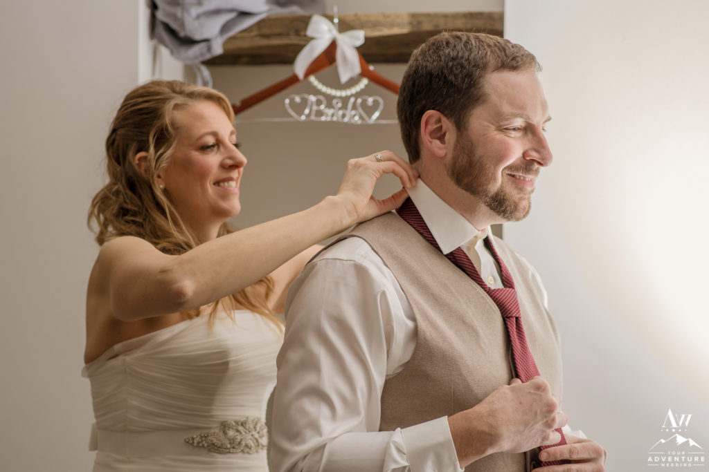 Bride helping her groom get ready for Iceland Elopement