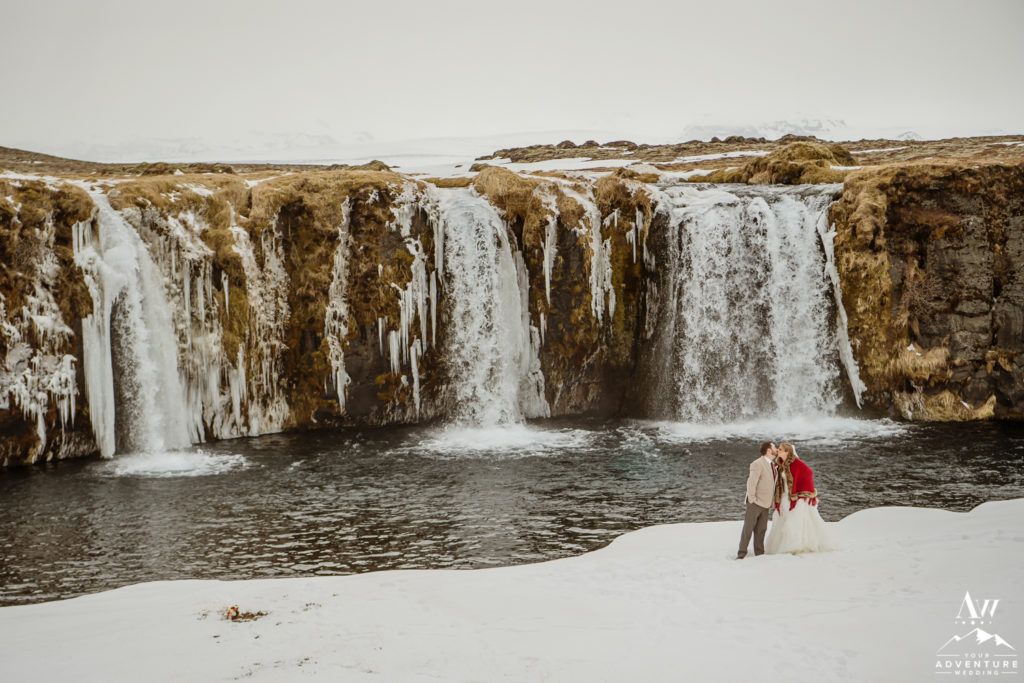 Couple kissing in front of a secret waterfall in Iceland
