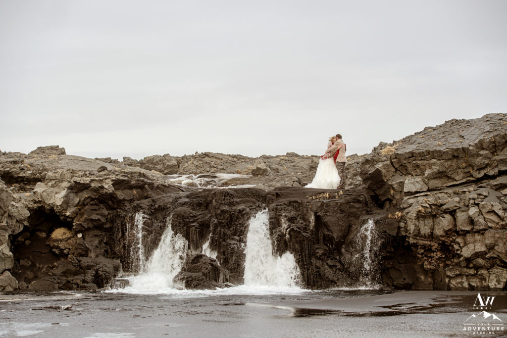 Iceland Elopement Couple hugging on top of a waterfall