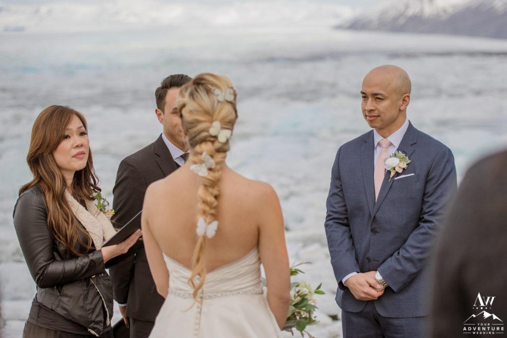 Groom looking at his bride during Iceland wedding ceremony at glacier lagoon