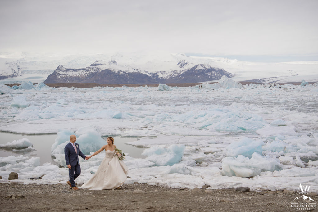 Couple walking in front of Iceland glacier lagoon