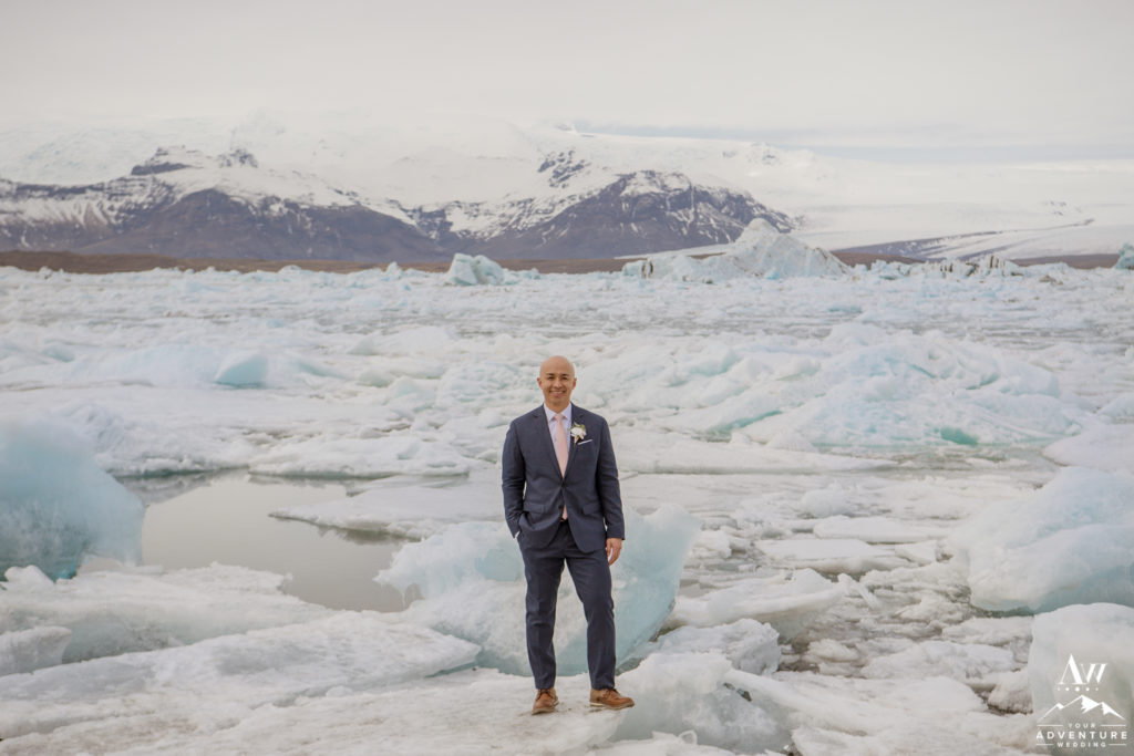 Groom standing on ice at glacier lagoon