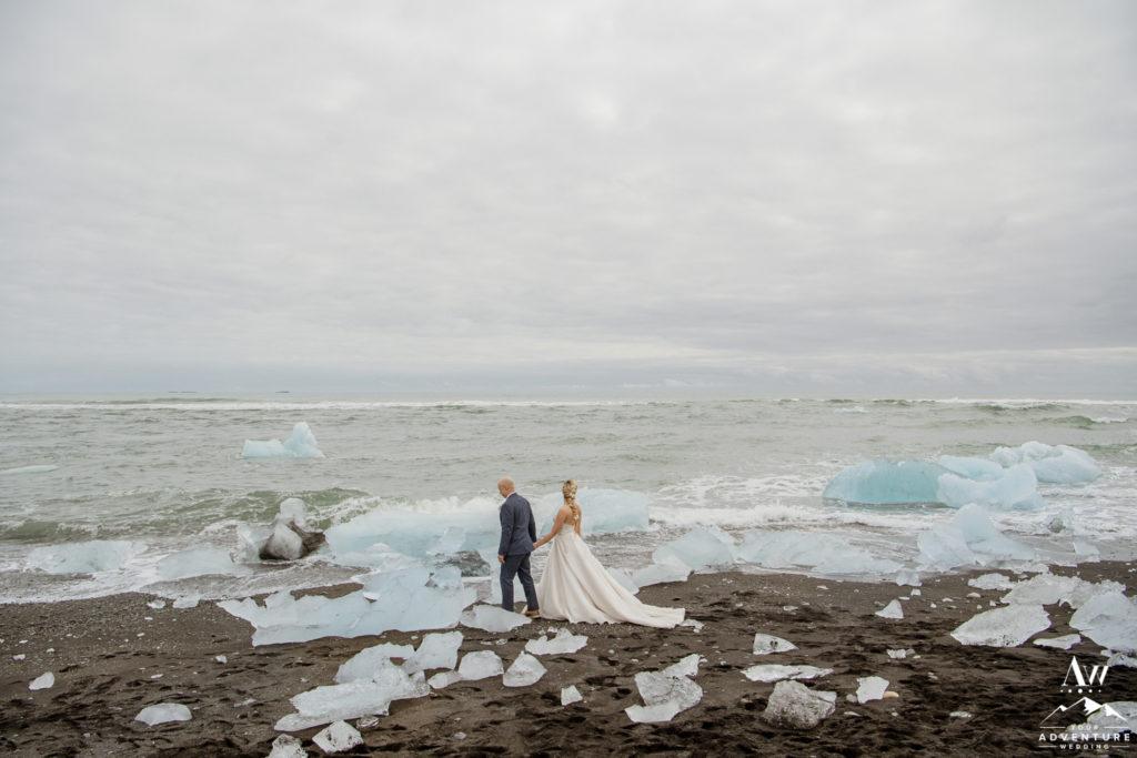 Iceland wedding couple walking on diamond beach