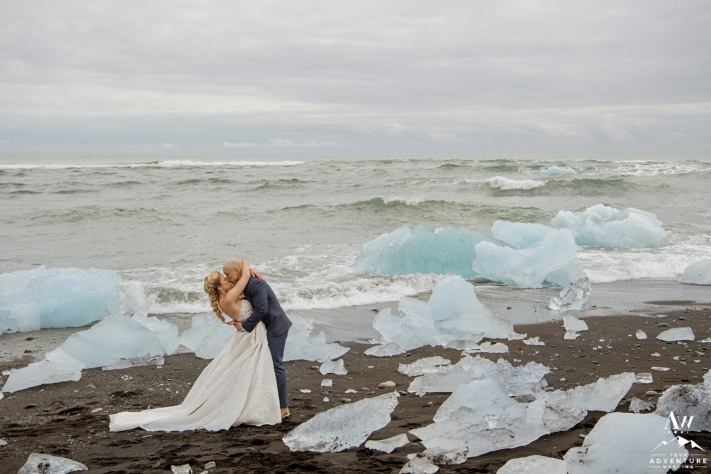 Iceland wedding couple kisses on diamond black beach