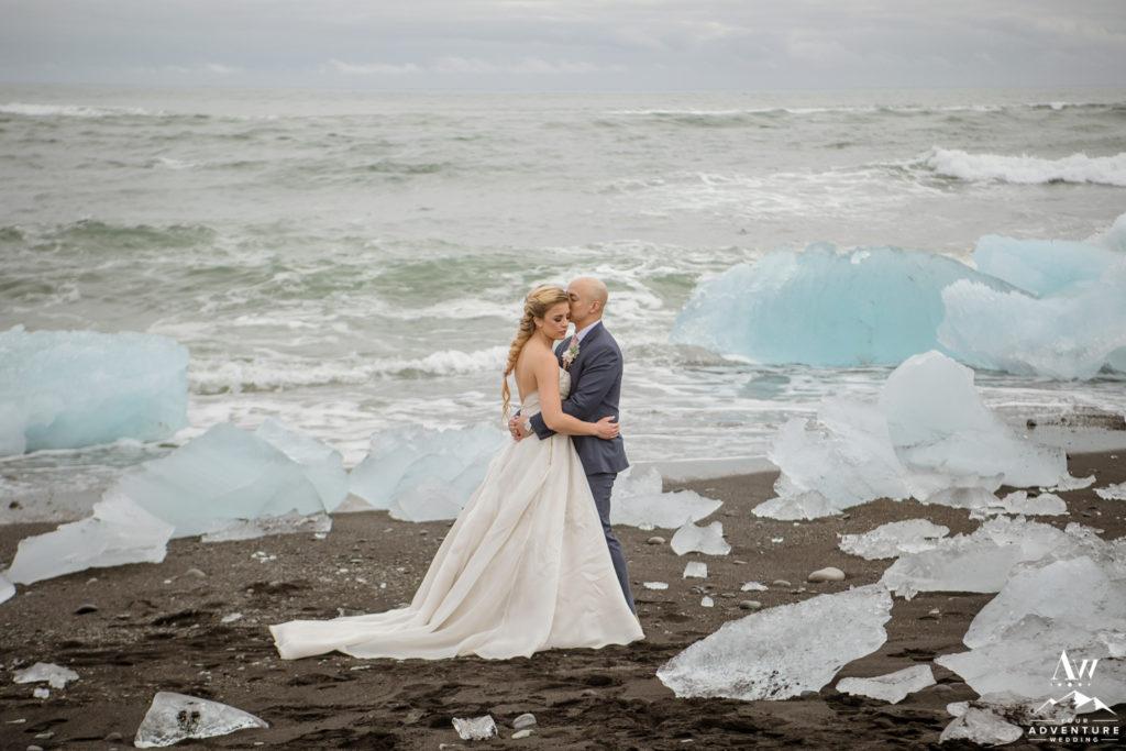 Iceland Wedding Groom kisses bride on the diamond beach
