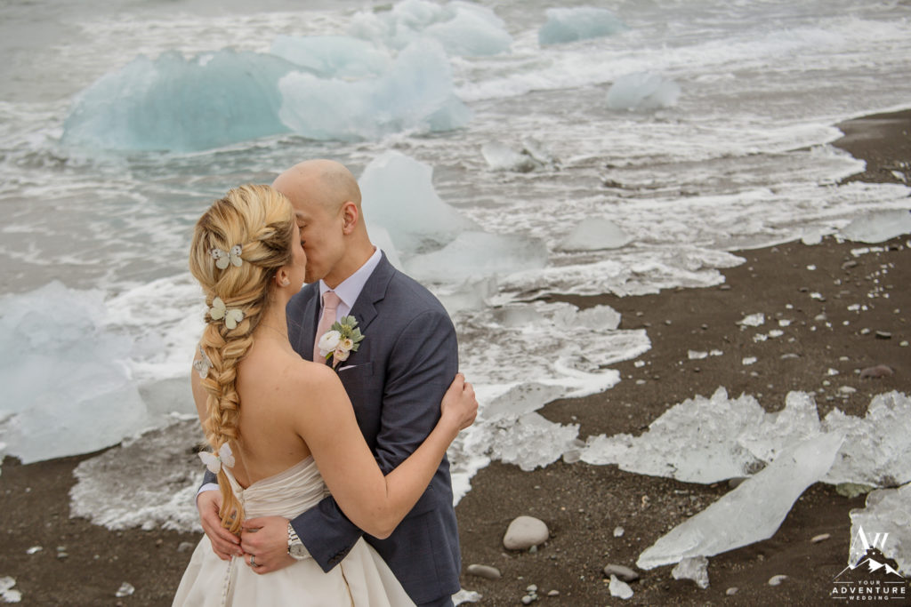 Couple kisses on Diamond Beach during Iceland wedding