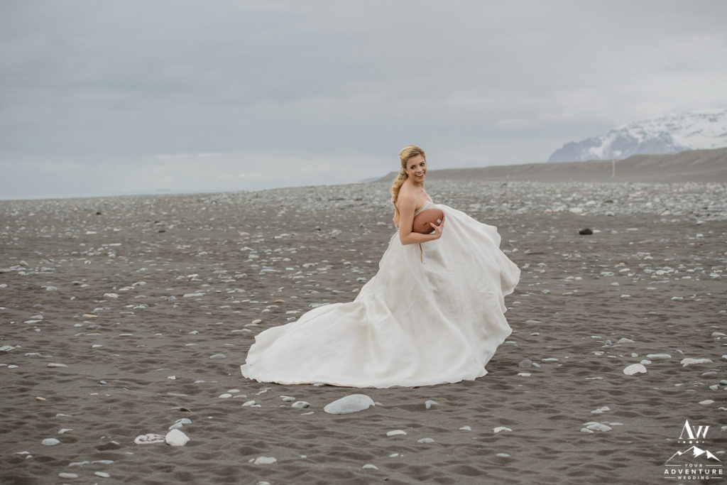 Bride smiling while playing American football on her Iceland wedding day