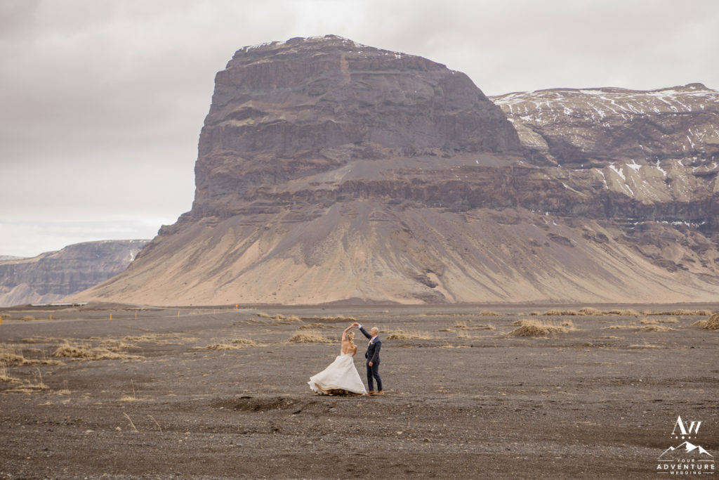 Couple dances in front of Lómagnúpur during Iceland wedding adventure