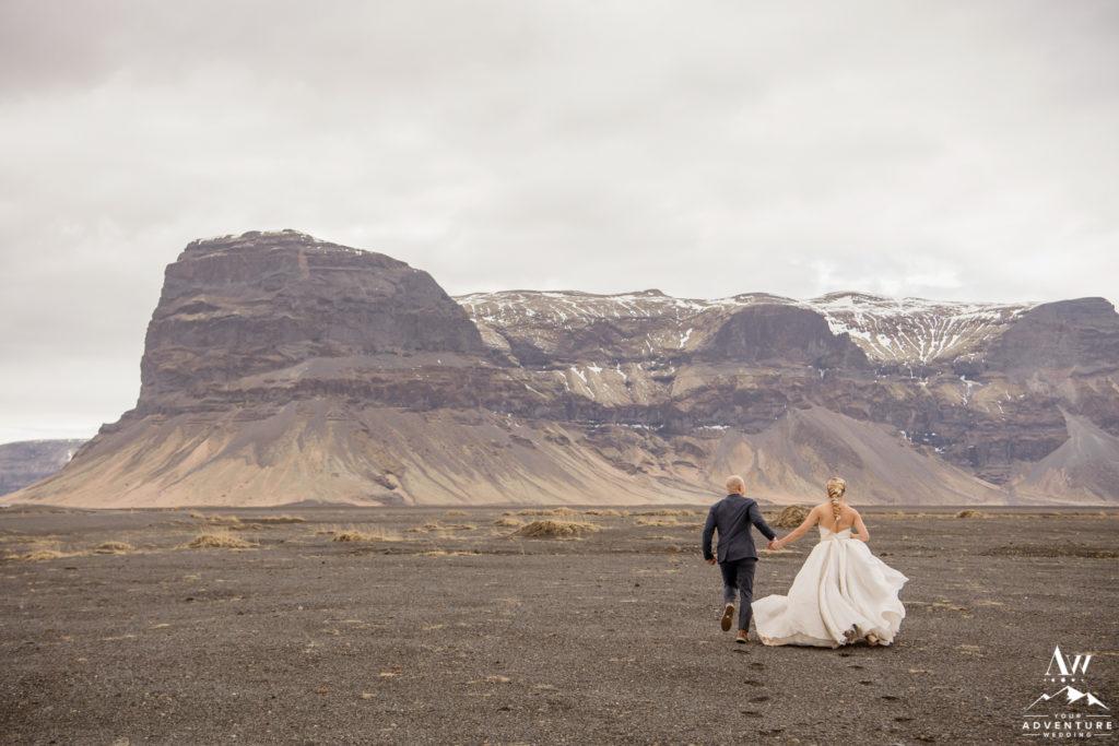 Iceland wedding couple runs towards Lómagnúpur mountain