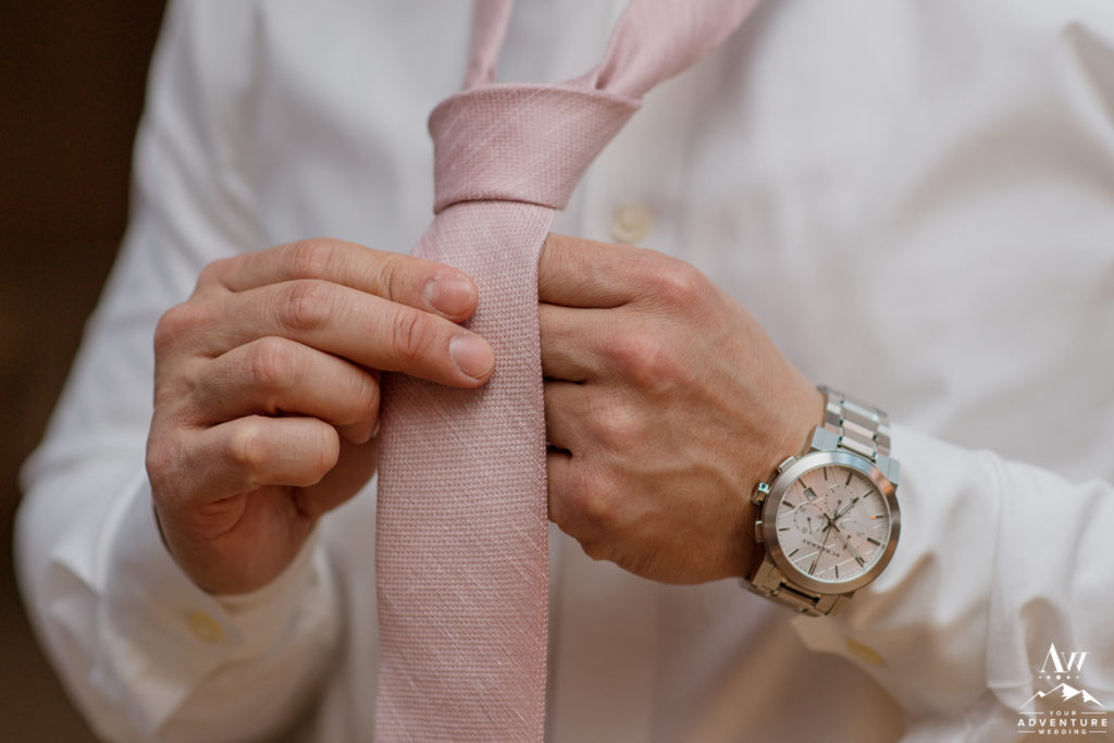 Groom tying his tie before Iceland wedding day